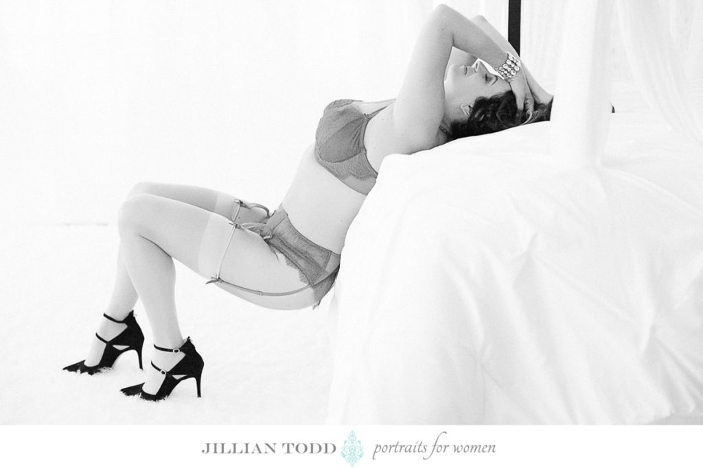 woman reclining on bed by roseville boudoir photographer