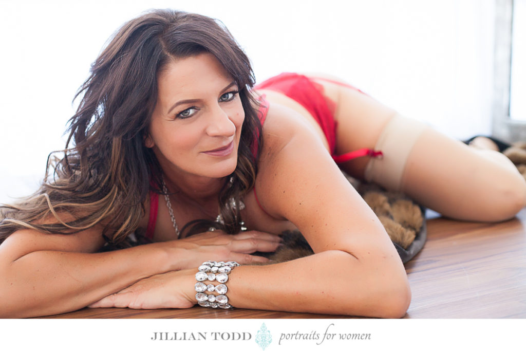 brunette woman laying on fur blanket and red lingerie by roseville boudoir photographer