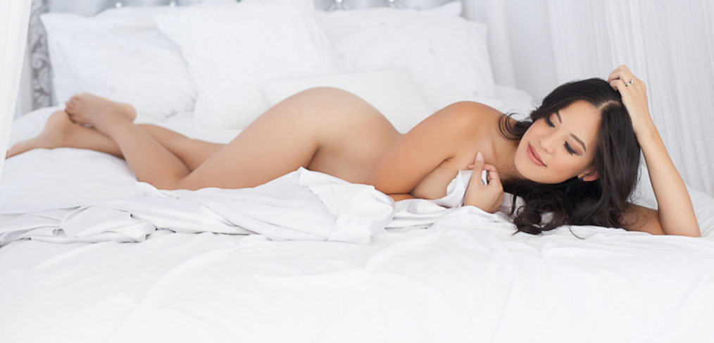 woman on bed wrapped in white sheets