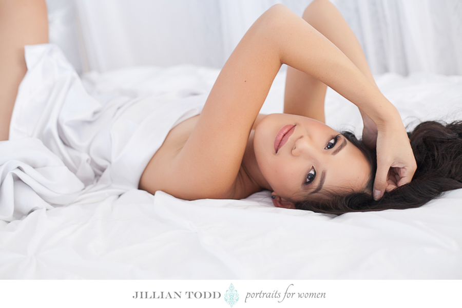 woman looking at camera on white bed wrapped in sheets